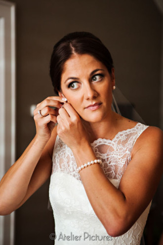 The bride looks stunning as she puts on her pearl earrings before her wedding ceremony in Corvallis
