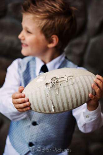 The ring bearer proudly holds the football shaped pillow with the wedding rings