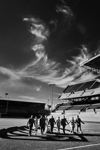 The bridal party strolls across the field at Reser Stadium in Corvallis on the wedding day
