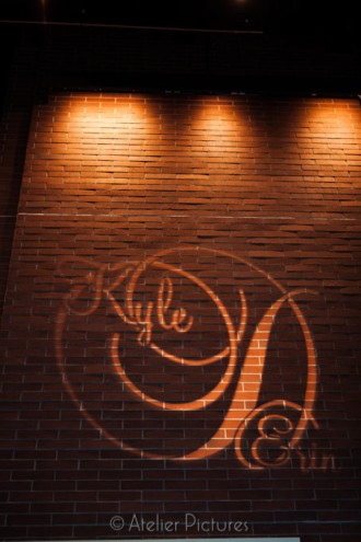 A gobo lights up the brick wall for the bride and groom at the Reser Stadium Wedding