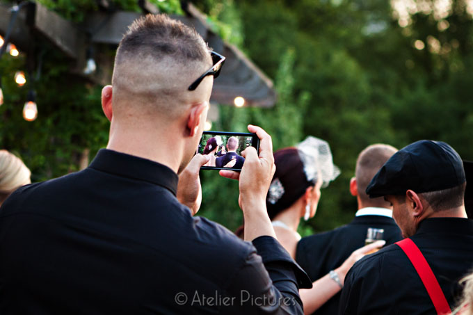 One of the wedding guests directs his camera toward the beautiful couple during the wedding toasts