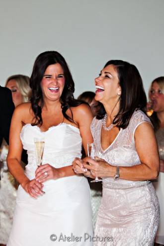The bride and mother of the groom laugh during the wedding toasts