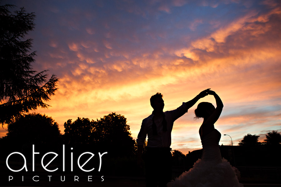 The sunset glows behind the silhouettes of the bride and groom as they dance together
