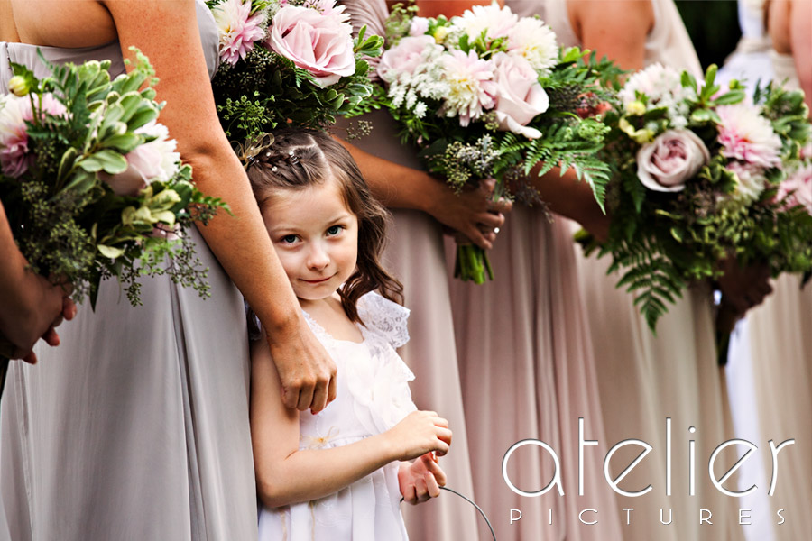 The flower girl glances at the camera and smiles for a brief moment