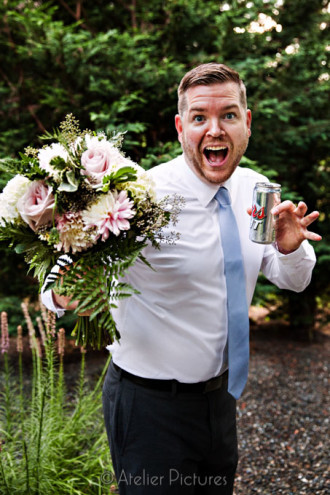 The groom was double fisting it with the bouquet and a beer