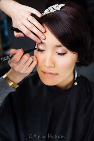 Finishing touches to the bride's eyeliner before her wedding ceremony