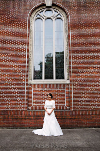 The bride stands in front of a huge brick wall at St. Mary's Cathedral