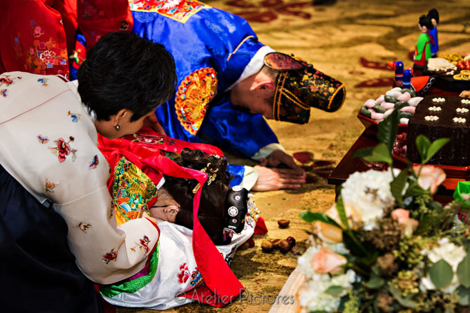 The bride and groom kneel on the ground during the Pyebaeck