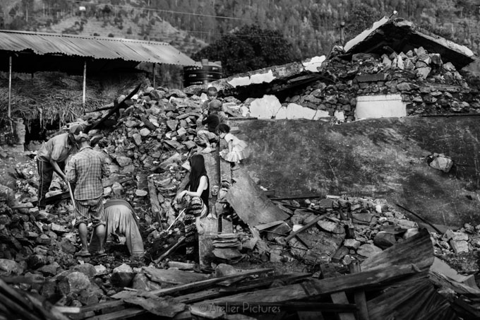 A family and neighbors sifting through the rubble of their home