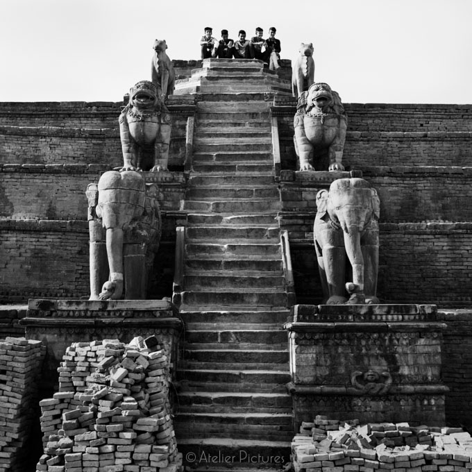 A group of young men sit atop the remains of a temple in Bhaktap